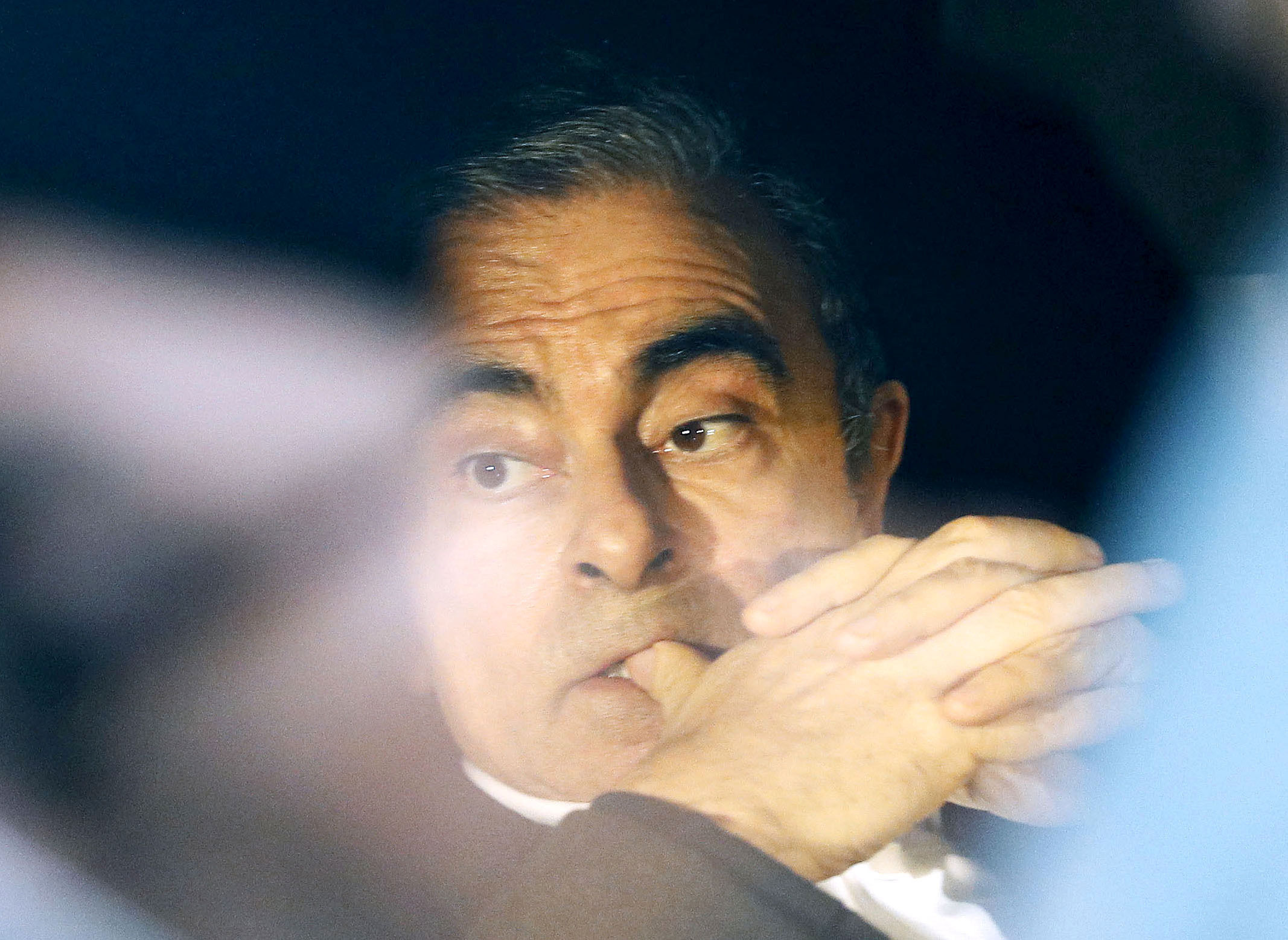 Carlos Ghosn rides in a car after being released from detention